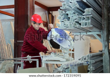 Worker Cutting PVC Profile with Circular Saw. Industrial Equipment. PVC windows and doors manufacturing. - stock photo