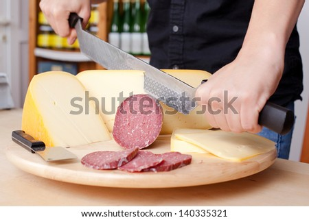 Worker cutting sausage and cheese on a wooden chopping board - stock photo