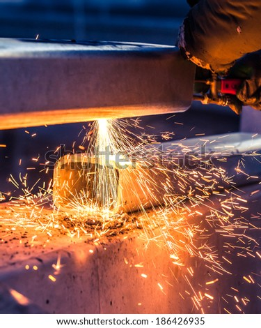 worker cutting steel pipe using metal torch and install roadside fence - stock photo