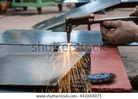 worker cutting steel sheet using metal torch in factory - stock photo