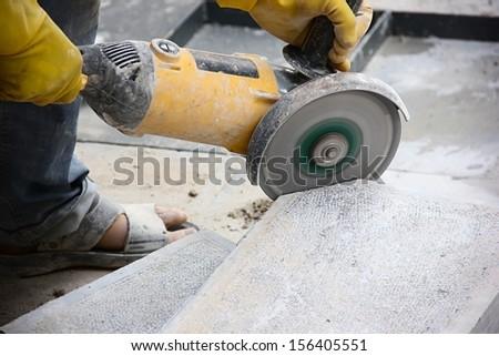 Worker cutting stone block by cutter machine. - stock photo