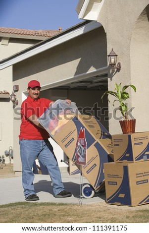Worker delivering cardboard boxes into a house - stock photo