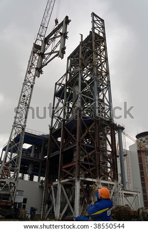 Worker directing a frame. Construction of chemical plant (urea producing) - stock photo