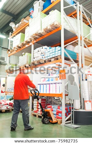 worker distributing goods in a warehouse with forklift truck loader - stock photo