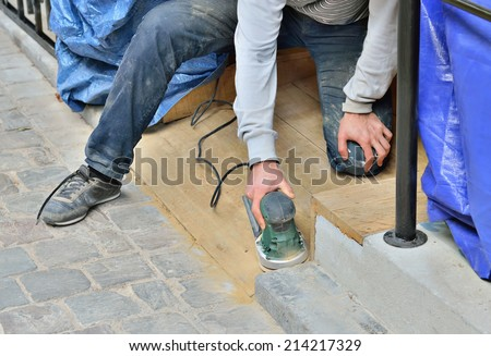 Worker doing polish of replaced staircase on restored entry of old building - stock photo