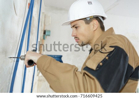 worker drilling on the wall