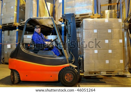 Worker driver of a forklift loader in blue workwear at warehouse with cardboard boxes on pallet - stock photo