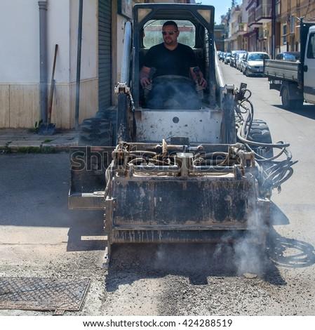 worker driver Skid steer remove Worn Asphalt during repairing Road Works - stock photo