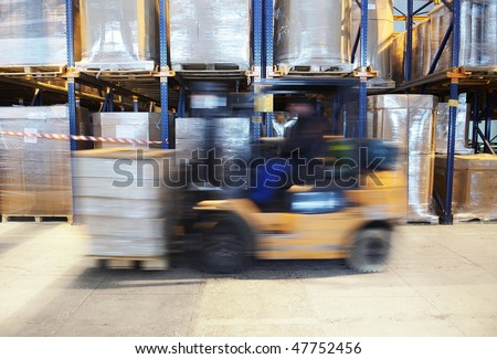 worker driving a forklift loader in warehouse with load on the pallet - stock photo