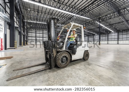 worker driving a forklift through a warehouse in a factory - stock photo