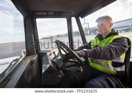 Worker Driving Towing Truck On Runway