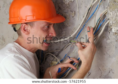 Worker electrician teeth compresses dangling wires - stock photo