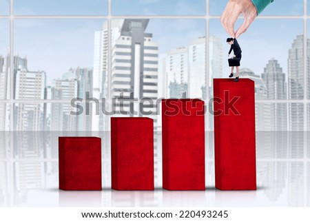 Worker exploitation concept with hand put businesswoman on chart