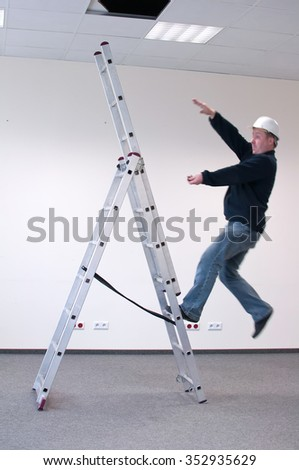 worker fell from a ladder - accident at work - stock photo