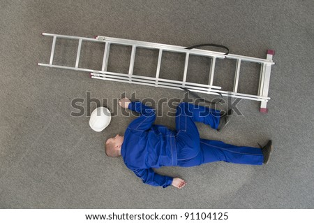worker fell from a ladder and lies on the floor - stock photo