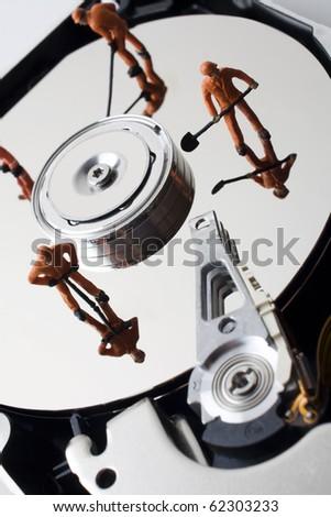 Worker figurine on hard drive - stock photo
