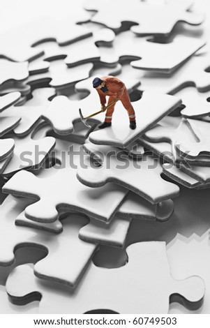 worker figurine on puzzle pieces - stock photo