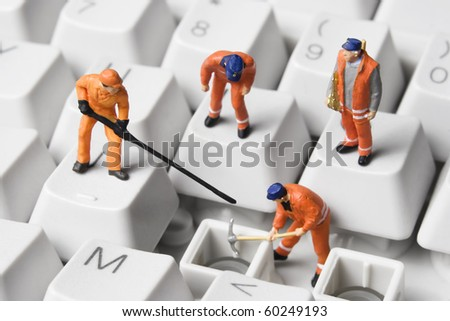 Worker figurines posed to look as though they are working on a computer keyboard. - stock photo