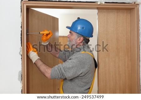Worker fix door hinge with screwdriver, wearing gloves and helmet - stock photo