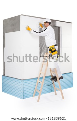 Worker fixing an insulation panel - stock photo