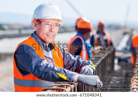 worker fixing steel rebar at building site