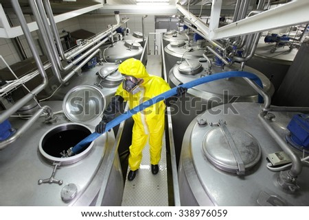 worker fully protected in yellow uniform,mask,and gloves filling large silver tank in factory