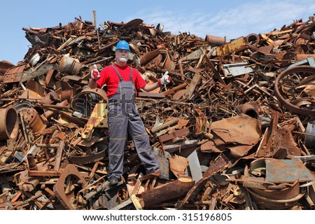 Worker gesturing heap of scrap metal ready for recycling, thumbs up