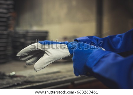 Worker getting on a pair of protection gloves.