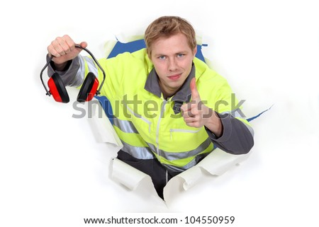 Worker giving the thumbs up to ear defenders - stock photo