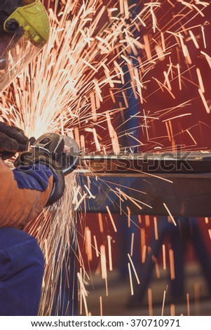Worker grinding a metal plate - stock photo