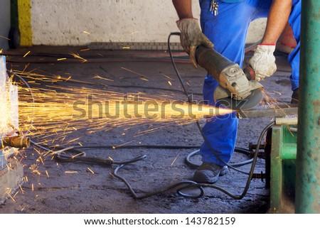 Worker grinding steel - stock photo
