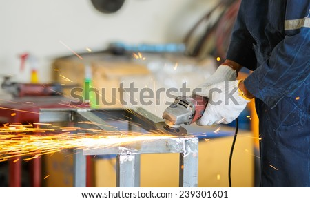 worker grinding steel by grinding machine - stock photo