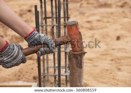 Worker hammering eucalyptus pointed at construction site - stock photo