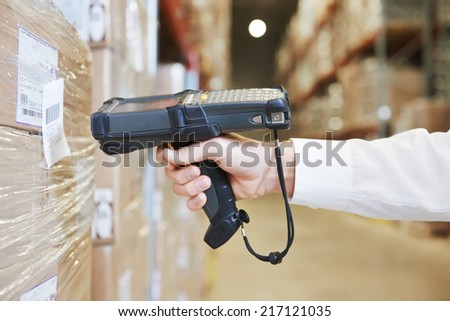 worker hand man scanning package with warehouse barcode scanner in modern storehouse - stock photo