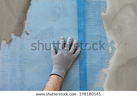 Worker hand placing mesh over styrofoam insulation and mortar - stock photo