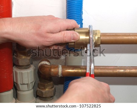 Worker hands fixing heating system with a special tool - stock photo