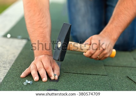 Worker hands installing bitumen roof shingles - fastening one with nails, closeup - stock photo