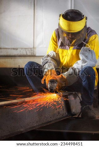 Worker hard work Electric wheel grinding on steel structure in factory with dramatic light - stock photo