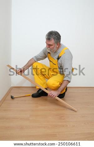 Worker hold batten for laminate floor and hammer,  floating wood tile - stock photo
