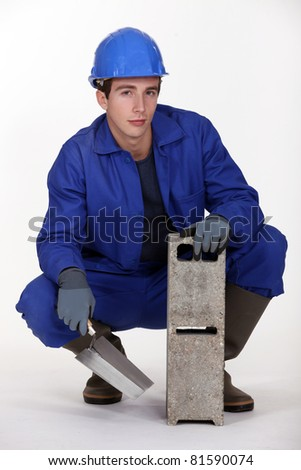 Worker holding a cinder block and trowel - stock photo