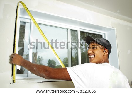 Worker holding a tape measure against wall to take measurement - stock photo