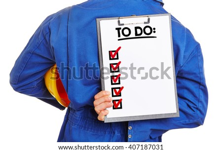 Worker holding a To Do list on a clipboard behind his back - stock photo