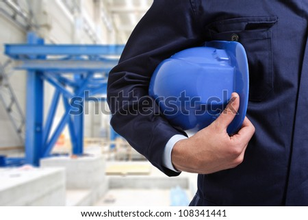 Worker holding an helmet in a construction site - stock photo