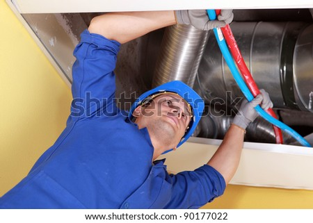 Worker holding blue and red pipes under air ducts - stock photo