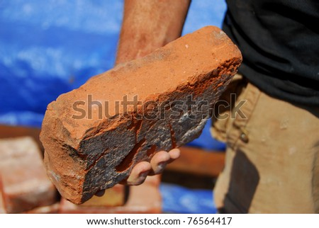 Worker holding brick - stock photo