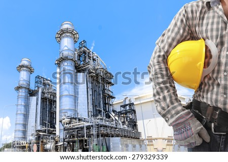 Worker holding hard hat for working at equipments and machinery with modern thermal power plant in refinery - stock photo