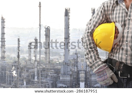 Worker holding hard hat for working at oil refinery petrochemical industrial plant - stock photo