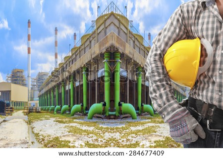 Worker holding hard hat working at cooling tower of Industrial power plant  - stock photo