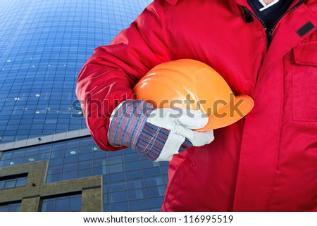 Worker holding hardhat against office building - stock photo