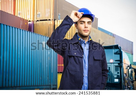 Worker holding his helmet in front of a stack of containers - stock photo